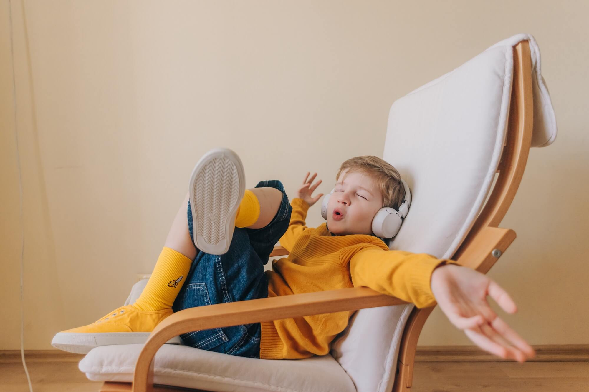 Emotional boy in yellow sneakers, with headphones.